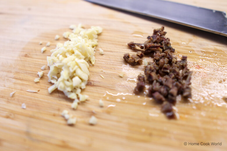 Minced garlic and minced anchovy on a wooden cutting board