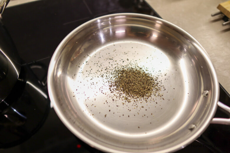 Pepper in a stainless steel frying pan for making Cacio e Pepe
