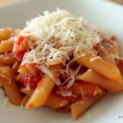 Penne pasta with tomatoes and hard Italian cheese