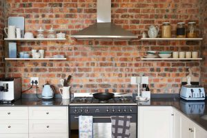 Photo of a home kitchen with a brick wall